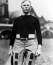 Heisman in his late forties wearing a jersey and lower pads, carrying his megaphone