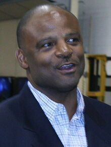 Color head-and-shoulders photograph of African-American man (Warren Moon) wearing a navy blazer and open-collar white tattersall shirt.