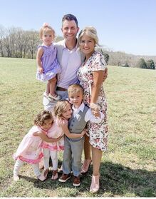 Chad and Erin standing on a sunny day. Chad is wearing a grey suit with white shirt and has his arm around Erin who is wearing a flowery white dress. Chad is holding Holland, who is wearing a purple dress. Standing directly in front of Chad and Erin is Carson, who is wearing a grey waistcoat and trousers. Carson has one arm around Brooklyn, who is hugging him, and Everly is hugging Brooklyn. Both Brooklyn and Everly are wearing pink dresses and white leggings