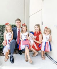 John, Alyssa and their four daughters outside on the 4th July. John and Alyssa are both crouched down, John is wearing a blue suit with white shirt and red tie, and Alyssa is wearing a red dress and nude heels. John's right arm (at the left of the photo) is around Lexi, who is leaning against his side. Allie is sitting on his other knee. Zoey is standing on the other side of Alyssa, and Maci is held on Alyssa's lap. the three older girls are wearing a white dress with a unicorn on the chest, and red white and blue tulle skirt. they also have a red bow in their hair and Allie is holding a pink clutch. Maci is wearing a frilly white patterned romper and has a blue bow on her head.