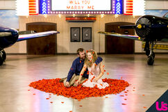 John and Abbie sitting in the midst of a heart of red petals