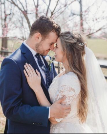 Jed and Katey on their wedding day, Jed in a blue suit and Katey in a white dress. Their foreheads are touching. Katey has her hand on his chest and Jed's hand is resting on her arm.