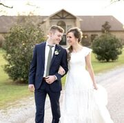 Justin and Claire walking along a path outside smiling at each other on their wedding day