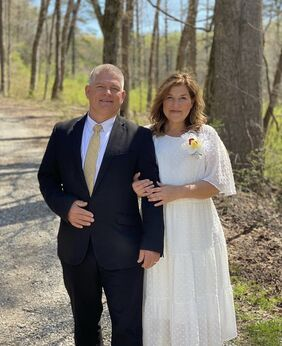 Gil and Kelly standing in a wood. Gil is wearing a dark suit with a white shirt and Kelly is wearing a white dress with a flower on