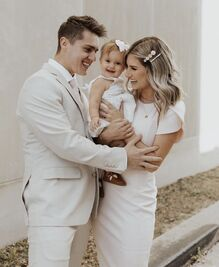 Carlin is wearing a white dress with white clasps in her hair. She is holding Layla (also in a white dress with a bow in her hair, who is smiling at the camera). Evan and Carlin are smiling at each other on either side of Layla. Evan is wearing a very pale grey suit.
