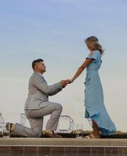 Nathan, down on one knee and wearing a grey suit, is holding the hand of Esther, who is smiling down at him. She is wearing a long blue flowey dress.