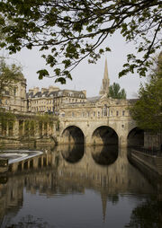 A three arch stone bridge with buildings on it, over water. Below the bridge is a three step weir and pleasure boat.