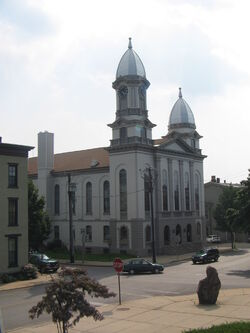 A formal building with arched windows and two domed towers is on a street corner near other less formal buildings. A car is parked in front of the formal building. Diagonally opposite are a stop sign and a small stone sculpture or monument.
