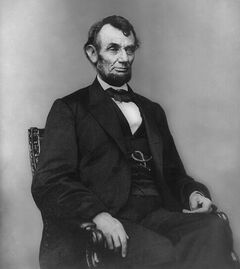 Middle-aged man in a beard posed sitting in a suit, vest and bowtie.