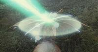 Grand King Ghidorah's force barrier repelling Mothra's Mineral Chest Beam.jpg