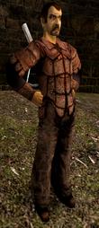Ubrany w skórzany pancerz mężczyzna z zarostem mający kuszę na plecach