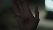 604-Symbol branded into Eve's hand from the Stick