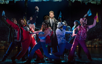 Phil surrounded by townsfolk in the Broadway production.png