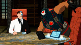 "Two-Face, a scarred man in a dress suit, sits at an executive chair while Bane, a large muscular man in a costume, tries to sit in another executive chair that is labelled ""In memoriam of Mr. Freeze"""
