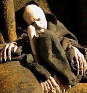 Obleczona w szmaty skrajnie wychudzona postać Voldemorta z długimi paznokciami