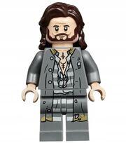 figurka LEGO przedstawiająca uśmiechniętego, długowłosego szatyna z brodą. Na czole i przy policzkach zaznaczone są zmarszczki. Figurka ubrana jest w szare, nieco podarte szaty więzienne z lekko odpiętą koszulą. Na klatce piersiowej widać dwa czarne tatuaże
