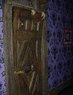 Skeletal hands on top of the door