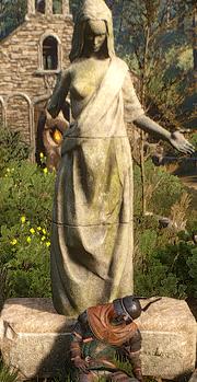 Dieses Bild zeigt die Skulptur der halbnackten Melitele, in ihrer zweiten Gestalt, der Frau, vor einem Friedhof in Weißgarten