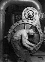 431px-Lewis Hine Power house mechanic working on steam pump.jpg