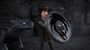 DOB - Hiccup uses his shield to defend himself from an incoming bola