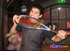 David bites a tennis racket.