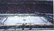 Two teams of many hockey players stand at either end of a rink built on top of a football field as thousands of people look on from the stands.