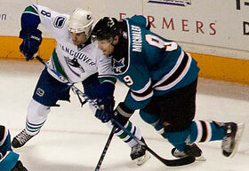 An ice hockey player dressed in a white and blue jersey attempting to impede another player dressed in a teal and black jersey with his stick.