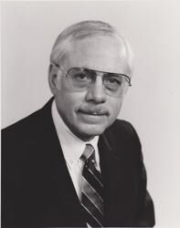 Photo of Hal Trumble wearing a dark jacket, white shirt, striped neck tie, and tinted glasses.