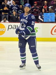 An ice hockey player wearing a blue and green jersey and a blue, visored helmet. He is following through with his hockey stick while standing upright.
