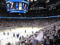 """An arena set up for ice hockey. Players skate towards center ice, while a larger crowd is waiving white towels. Over head is a jumbo-tron with an extreme close-up of a player looking seriously at the camera, above and below the picture is the word """"Believe"""" in white lights with a blue light background."""