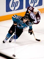An ice hockey player dressed in a teal and black jersey cradling the puck with his stick in mid-stride. An opposing player is in pursuit behind him.