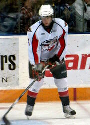 A teenage ice hockey player stickhandling a puck while standing still on the ice. His skates are shoulder-width apart and his eyes are downcast. He wears a white jersey with red and black trim, as well as a white, visored helmet.
