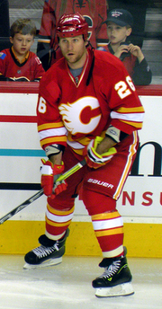 A player in a red uniform with yellow and white stripes at the waist looks into the distance.