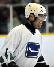 A side view of a middle-aged, Caucasian ice hockey player. He is wearing a white helmet and jersey with a blue and green logo of a horizontal hockey stick. He looking forward and smiling.