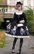 Slim-young-woman-in-a-short-pale-violet-wig-wearing-a-black-and-white-dress-with-cat-and-cross-patterns-gothic-lolita-attire-black-patterned-tights-and-a-blach-head-bow