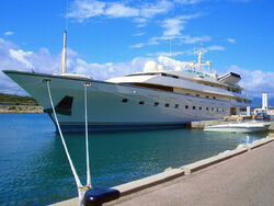 A large, sleek ship is moored at a quayside