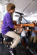Justin Bieber playing guitar at Nintendo World Store 2009