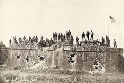 American troops raising the Flag at Fort San Antonio De Abad, Malate, Philippines (1899).jpg