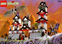 Zdjęcie. Model przedstawiający zamek i minifigurki. Jedna minifigurka unosi się w powietrzu dzięki lotni. Tło przedstawia góry o zachodzie słońca.