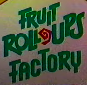A logo for the fictitious Fruit Roll-Ups Factory seen in various commercials- the text is green and the Roll-Up standing in for the dash is red.