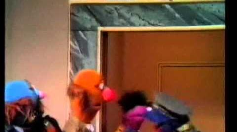 Grover as elevator attendant (in Malay)