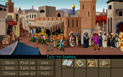 """A video game screenshot showing the two protagonists in the middle of a crowded marketplace. The lower part of the image shows a variety of objects on the right side and a number of verbs such as """"Pick up"""", """"Use"""" and """"Talk to"""" on the left side. The mouse cursor is pointing at Sophia, making the current command """"Talk to Sophia""""."""