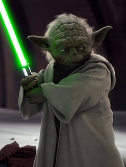 Yoda holding a lightsaber.