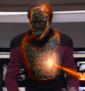 """""""Kieran MacDuff"""", a Satarran, as his Human disguise is partially removed by the impact of a phaser beam (2368)"""