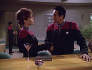 Chakotay and Archer shake hands at the bar of the a recreation of the Quantum Café, Archer's Klingon Martini rests on the bar top