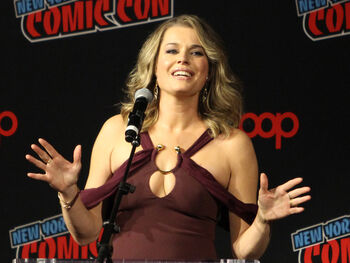 Romijn onstage at the New York Comic Con in 2018, speaking into a microphone