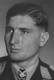 The head of a young man, shown in semi-profile. He wears a military uniform with a military decoration displayed at the front of his shirt collar. His hair is dark and short and combed to his right, his nose is long and straight, and his facial expression is emotionless; looking to the right of the camera.
