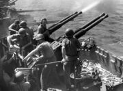 The gun crew operating these guns; four men handle ammunition while another yells over the blast from the guns. Spent shell casings litter the deck below.