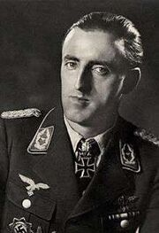 The head and shoulders of a man, shown in semi-profile. He wears a military uniform with various military decorations and an Iron Cross at the front of his shirt collar. His hair is dark and short and combed back, his nose is long and bent and his mouth is thin; he is looking into the camera