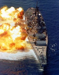 A large warship with guns pointed to the left; fire and smoke can be seen emanating from the gun barrels. Below the ship the dark blue water has taken on a white color owing to the disturbance in wind pressure from the firing of the guns.